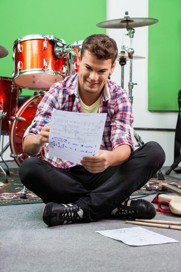 Примечания сочинительства барабанщика на бумаге пока сидящ дальше стоковое изображение rf