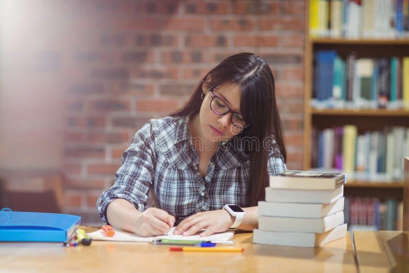 Примечания сочинительства студентки в библиотеке стоковое изображение