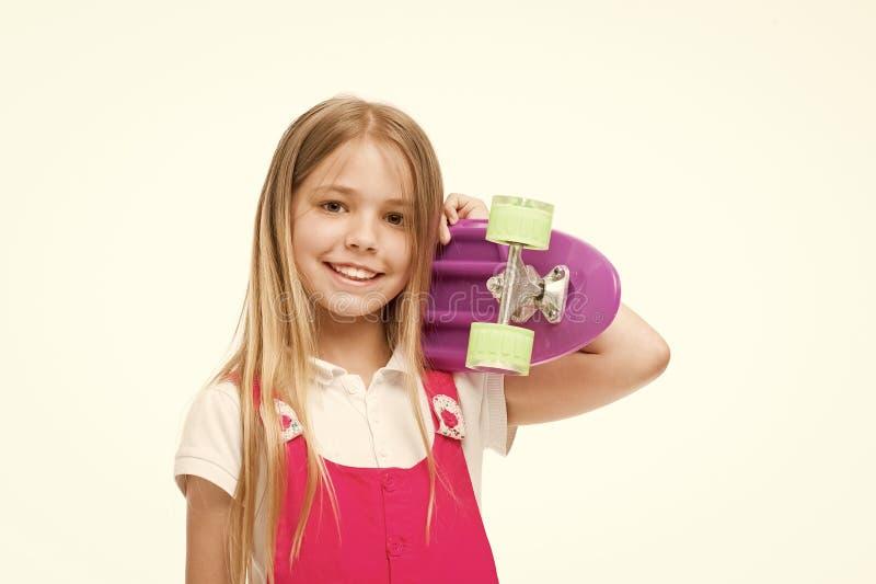 ( Принесенный для того чтобы быть девушкой конькобежца Небольшая улыбка девушки с доской конька изолированной на белизне стоковые изображения