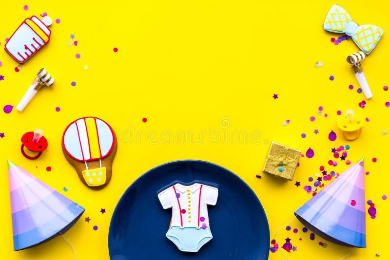 принесенный младенцем ливень карточки мальчика новый Печенья в форме аксессуаров для ребенка, шляп партии и confetti на желтом вз стоковое изображение