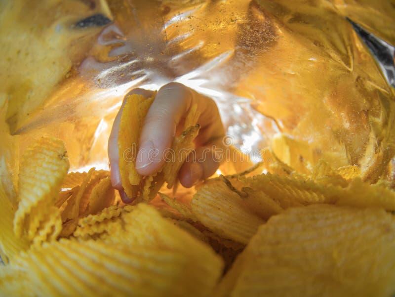 Принимать кудрявые картофельные стружки внутри пакета стоковые изображения rf