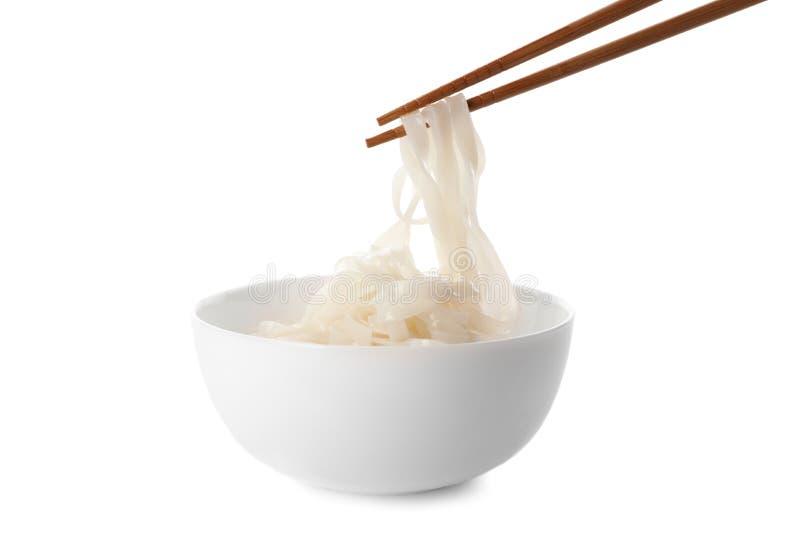 Принимать лапши риса с палочками от шара на белой предпосылке стоковые изображения rf