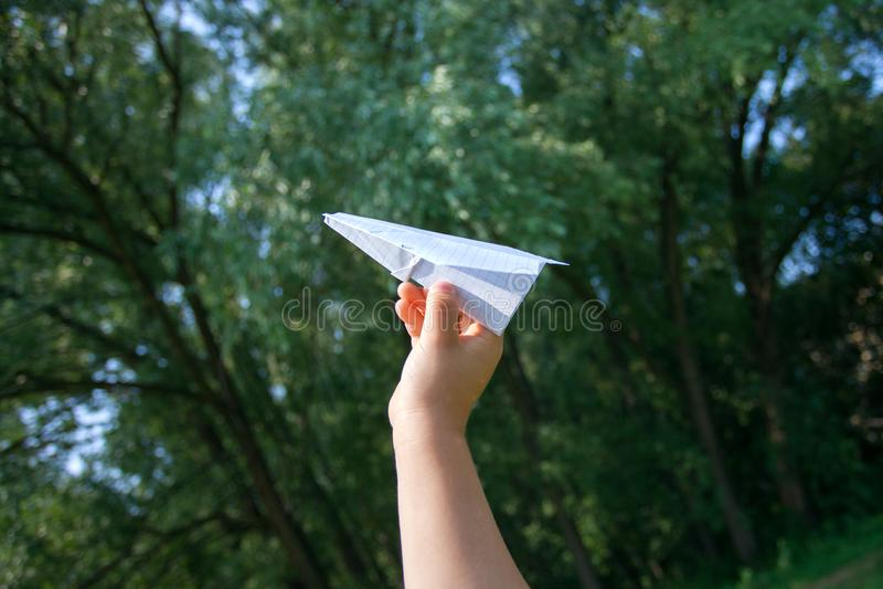 Принимать полет! Вручите держать бумажный самолет в небе и зеленый сад, концепцию лета, детства, мечтая стоковое фото rf