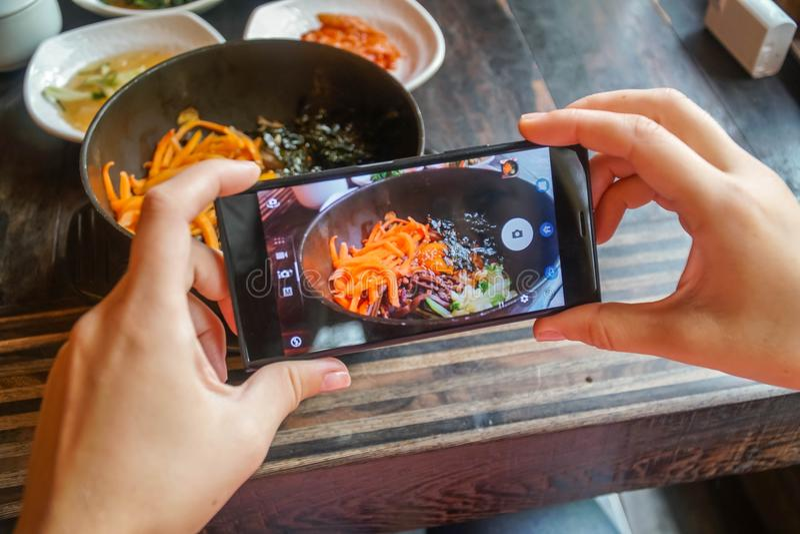 Принимать фото еды традиционного корейского Bibimbap блюда служил вместе с малыми гарнирами clled banchan на мобильном телефоне стоковые фотографии rf