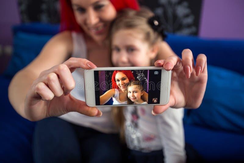 Принимать фото с мамой и дочерью мобильного телефона стоковое фото rf