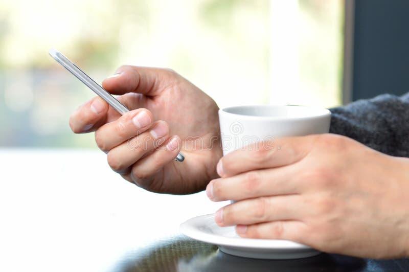 принимающ кофе и использующ смартфон дома стоковое изображение rf