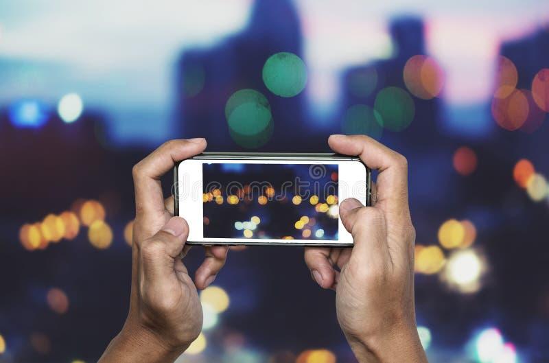 Принимающ фото умным телефоном, руки держа smartphone принимая Bokeh освещают стоковая фотография rf