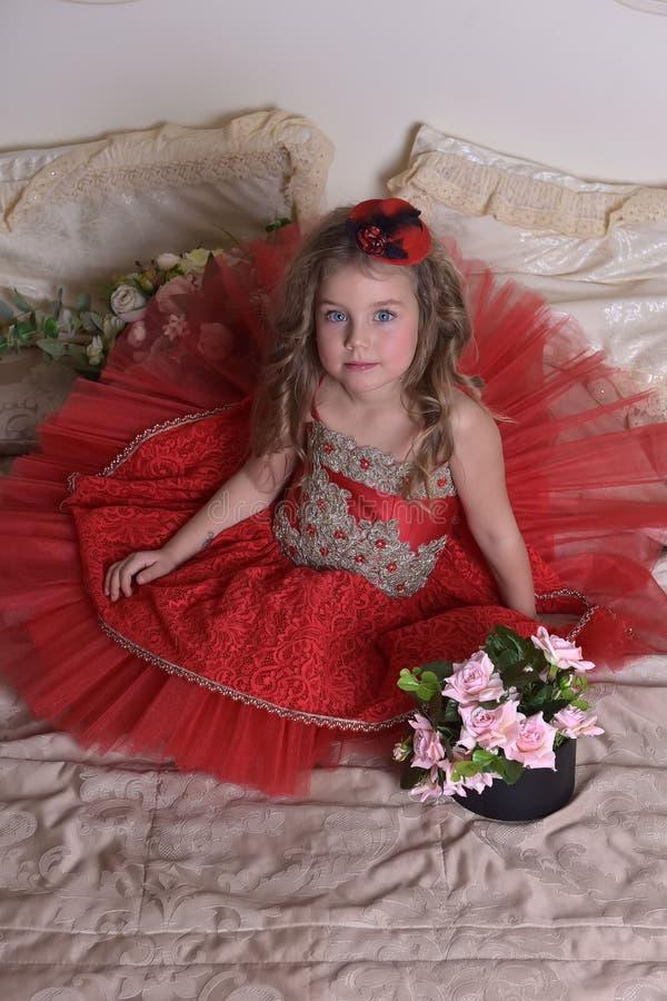 Принцесса маленькой девочки в красном платье и шляпе сидит на софе w стоковая фотография rf