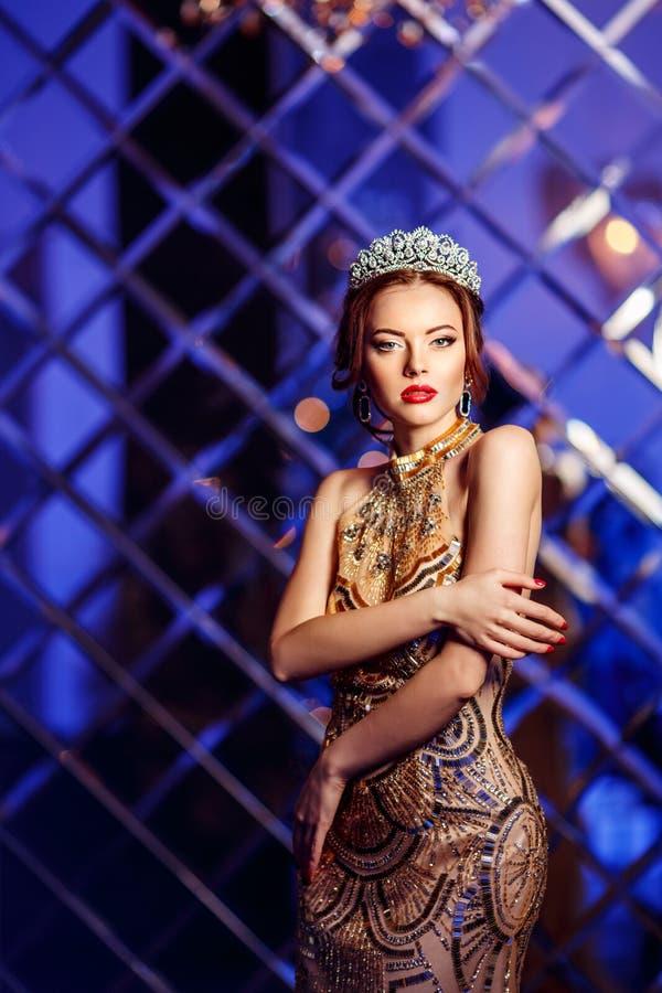 Принцесса ферзя женщины в кроне и платье люкса, backgr партии светов стоковое фото