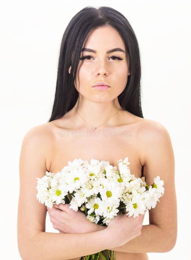 Принципиальная схема внимательности кожи Девушка на спокойной стороне стоит нагой и держит цветки стоцвета перед женщиной комода  стоковые изображения