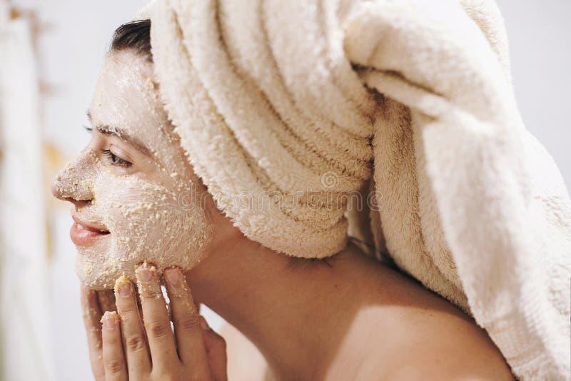 Принципиальная схема внимательности кожи Молодая счастливая женщина в полотенце делая лицевой массаж с органической стороной scru стоковое изображение rf