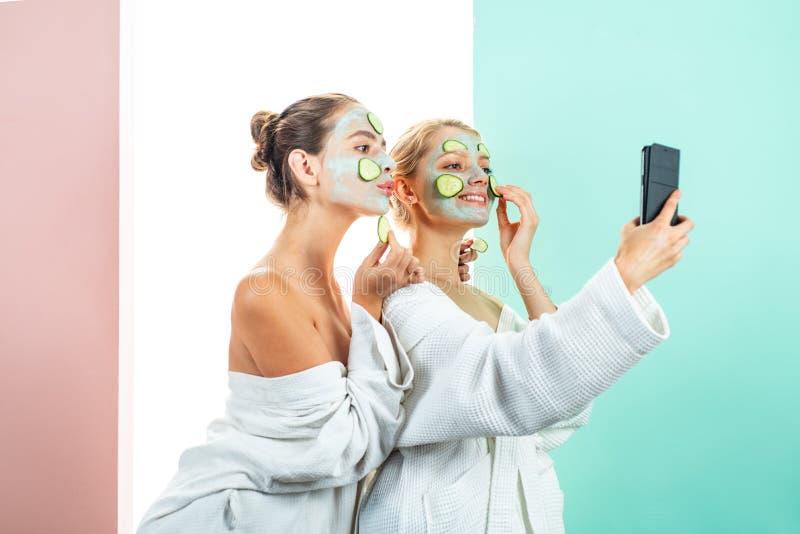 Принципиальная схема внимательности кожи cream сторона Портрет 2 красивых молодых женских моделей с естественным лицевым макияжем стоковое изображение rf