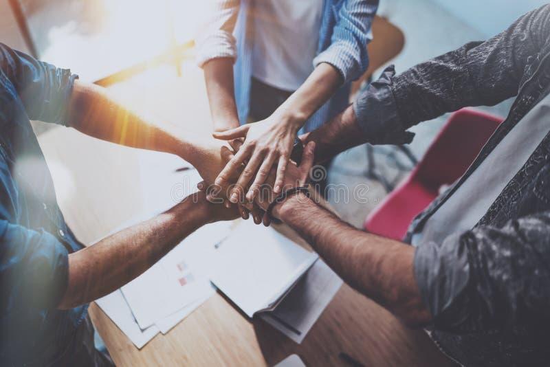 Принципиальная схема дела сыгранности Взгляд группы в составе 3 сотрудника соединяет руку совместно во время их встречи горизонта стоковое фото rf