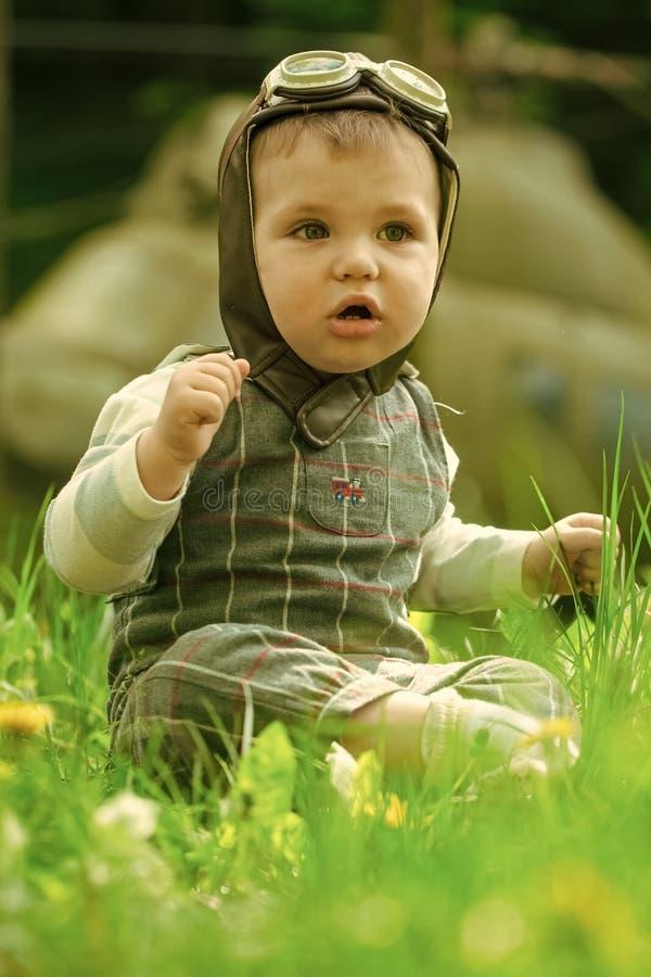 принципиальная схема детства счастливая Путешествовать и приключение Малыш в пилотном шлеме при стекла сидя в зеленой траве стоковое изображение