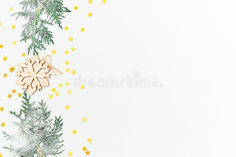 Принципиальная схема рождества Ветви ели и деревянное украшение с золотым confetti на белой предпосылке Плоское положение, взгляд стоковые изображения rf