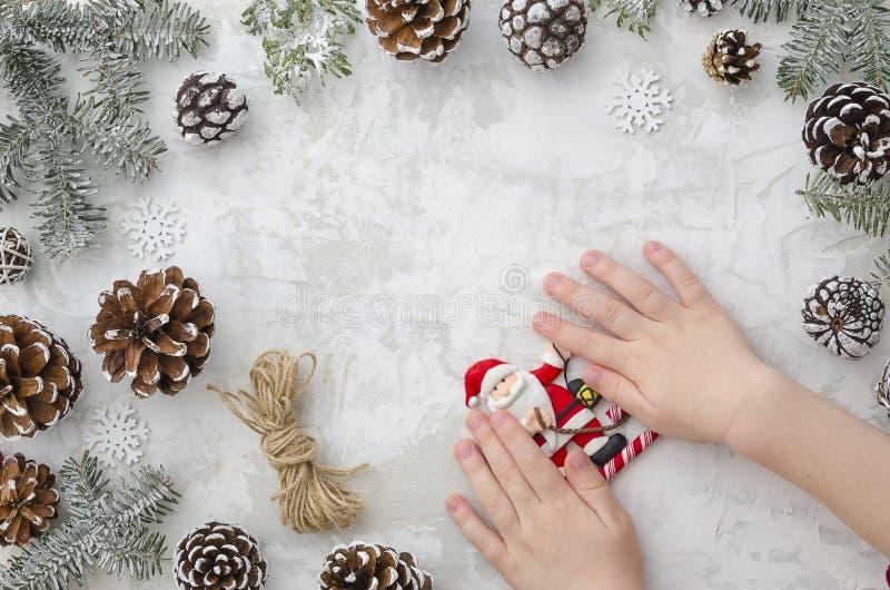 Принципиальная схема рождества Руки плоских детей положения держат игрушку Санта Клауса, конусы, ветви ели, веревочку и снежинки  стоковые фото