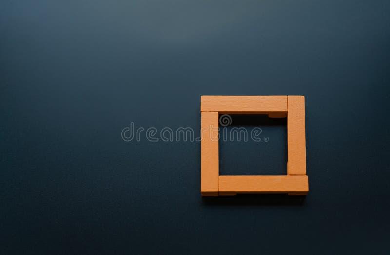 Принципиальная схема сыгранности группа в составе деревянный квадрат на черных предпосылках с космосом экземпляра стоковая фотография rf