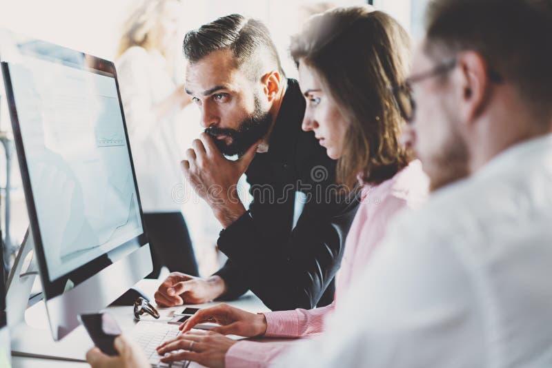 Принципиальная схема сыгранности Молодые творческие сотрудники работая с новым startup проектом в современном офисе люди 3 группы стоковое фото