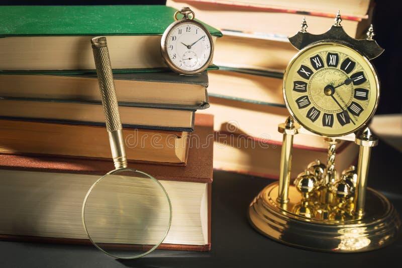 Принципиальная схема словесности Лупа около винтажных часов и старых книг против черной предпосылки стоковая фотография rf
