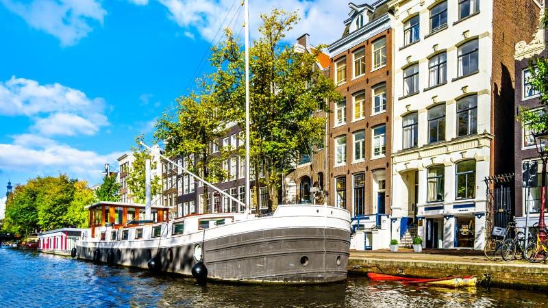 Принц Канал Prinsengracht с ним много исторических домов и реклама и прогулочные катера в центре Амстердама стоковая фотография rf