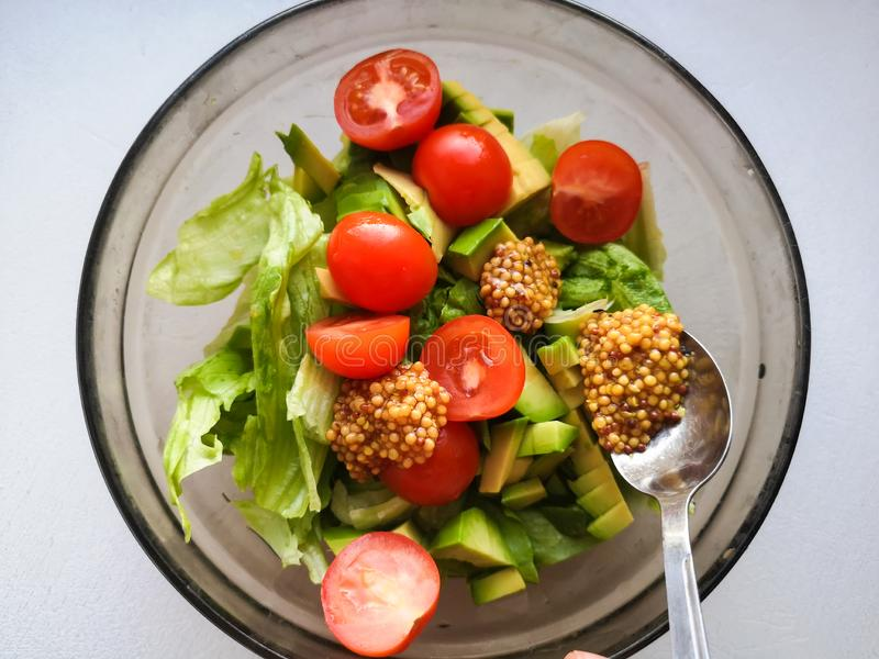 Приправа для салата овоща, добавляя французский мустард к салату овоща, еда Vigatarian, здоровая еда Женский лить повара прованск стоковые изображения rf