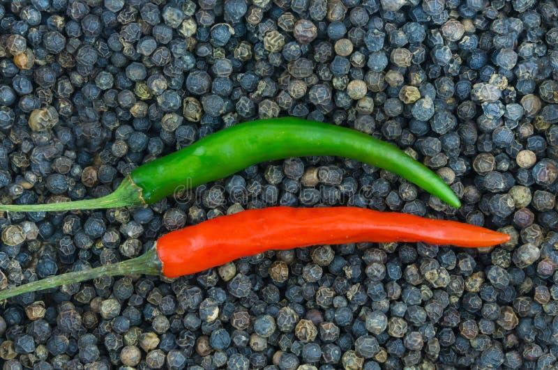 Приправа параллельных красных зеленых стручков горячих перцев длинных низкопробная для мяса давая питье к предпосылке ба черных п стоковое изображение rf