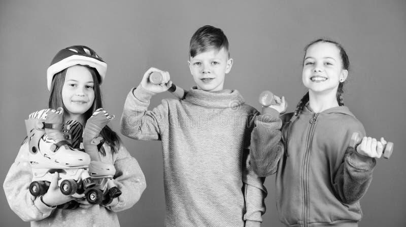 Присоединяться к активному образу жизни Девушки и мальчик детей с гантелями и бейсбольной битой коньков ролика Активная концепция стоковое изображение