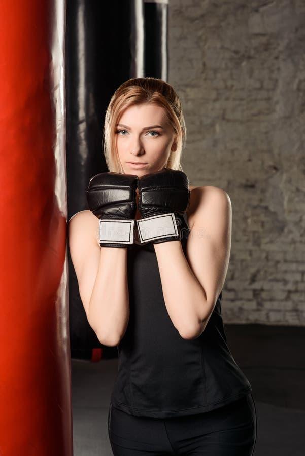 Приспособьте и уменьшите белокурую тренировку дамы в спортзале украшенном в белых, красных и черных цветах, в защитительной стойк стоковые изображения rf