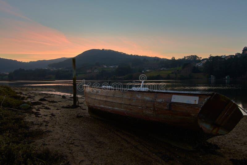 Приставанная к берегу шлюпка в заходе солнца стоковое изображение rf