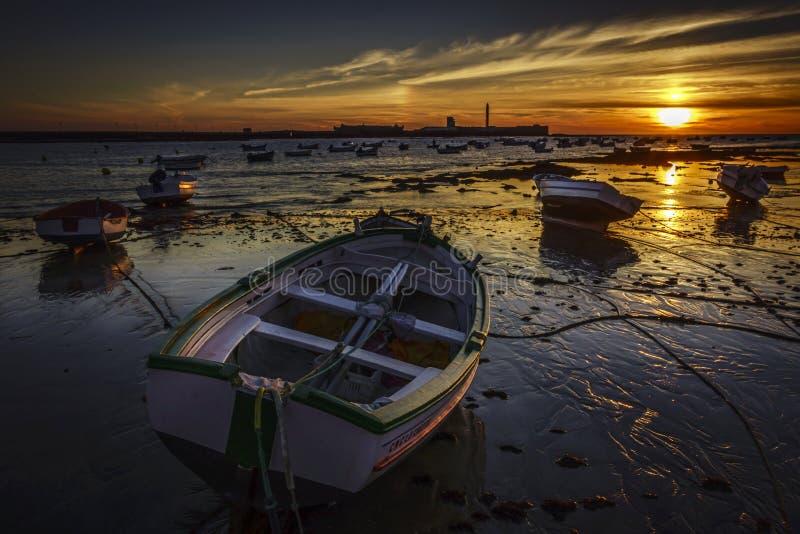 Приставанная к берегу шлюпка на заходе солнца Кадисе Испании стоковое изображение rf