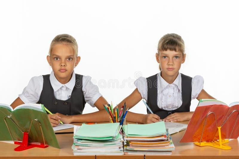 Пристальный взгляд 2 школьниц умышленно и emotionlessly в рамку стоковое изображение rf