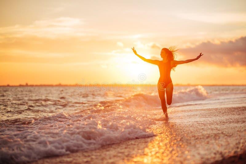 пристаньте беспечальную принципиальную схему к берегу танцуя здоровая живущая женщина витальности каникулы захода солнца стоковая фотография rf