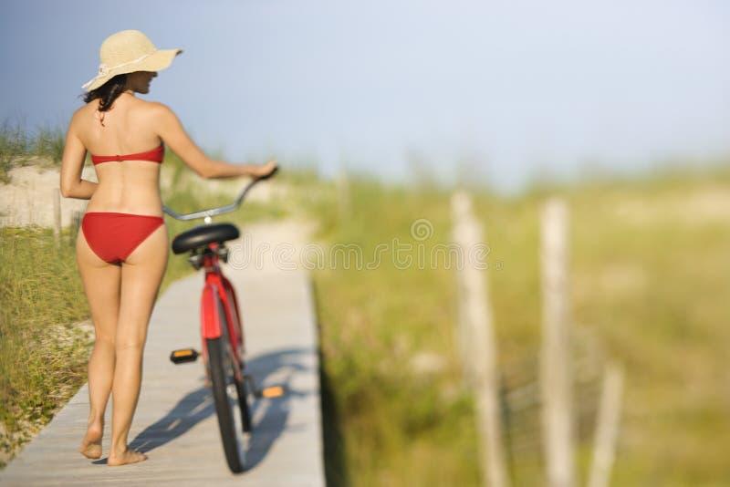 пристаньте женщину к берегу велосипеда стоковое фото rf