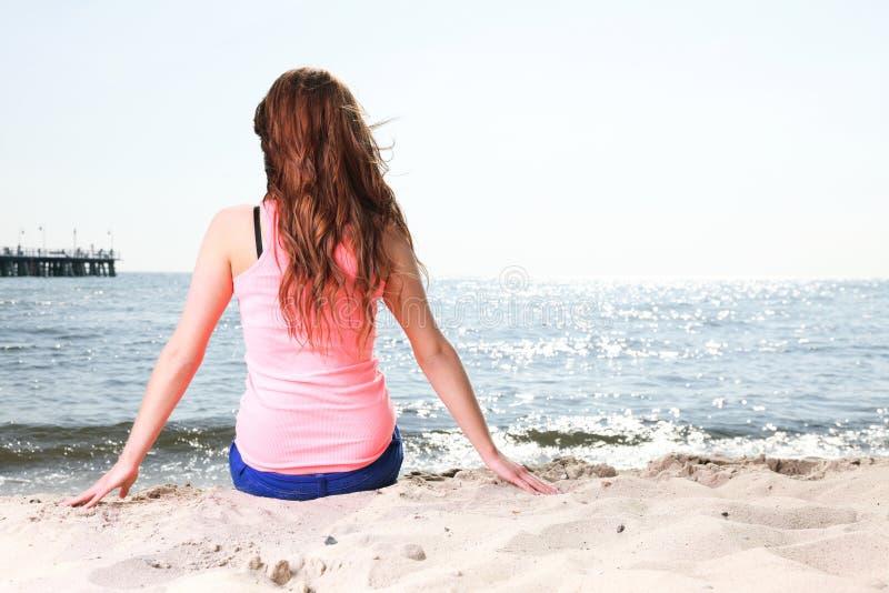 Пристаньте женщину к берегу праздников наслаждаясь песком солнца лета сидя стоковое фото