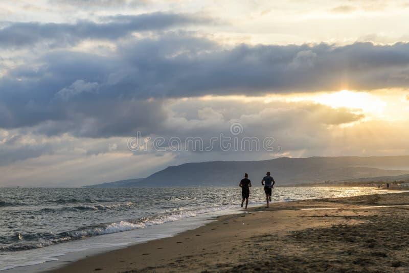пристаньте заход солнца к берегу человека идущий стоковое фото