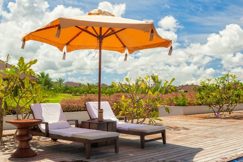 Пристаньте кресла для отдыха к берегу с полотенцами под зонтиком на poolside o стоковое изображение rf