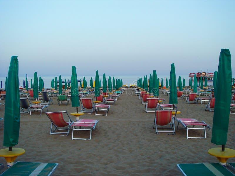 Пристаньте к берегу в аккуратно помещенных утре, пустых креслах для отдыха и навесах яркого цвета, стоковое фото rf