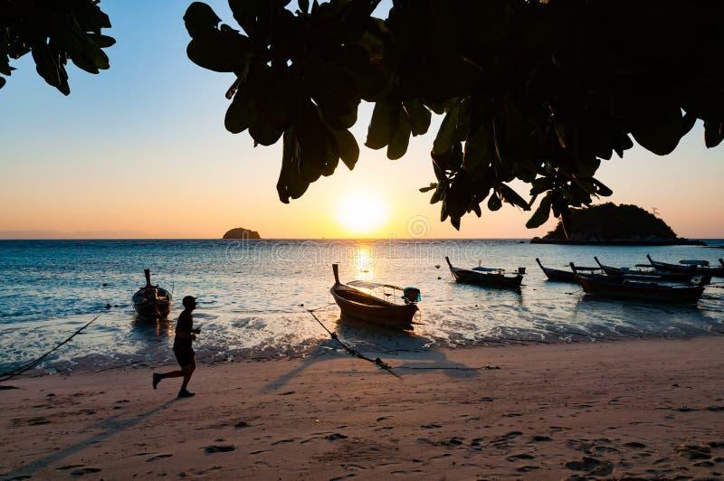 Пристаньте к берегу в утре с jogging человека и шлюпке с восходом солнца в l стоковая фотография