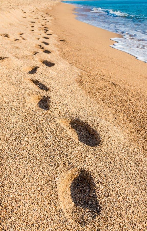 пристаньте песок к берегу следов ноги стоковое фото