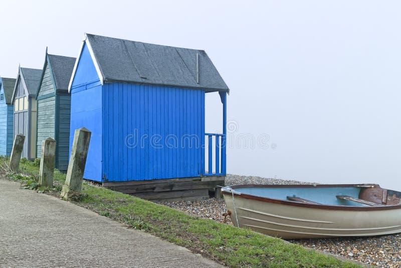 Пристаньте хаты и рыбацкую лодку к берегу на английском взморье на туманный день стоковые изображения