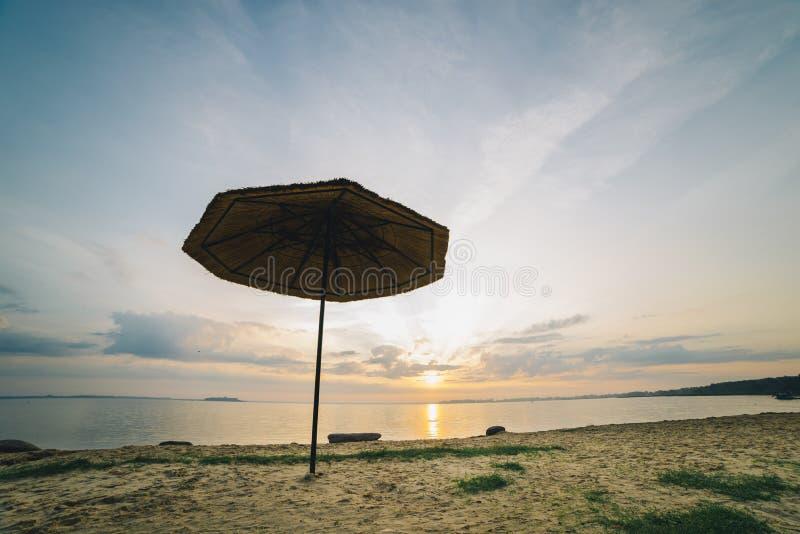 Пристаньте umbrellu к берегу на взморье с восходом солнца на предпосылке стоковое фото rf