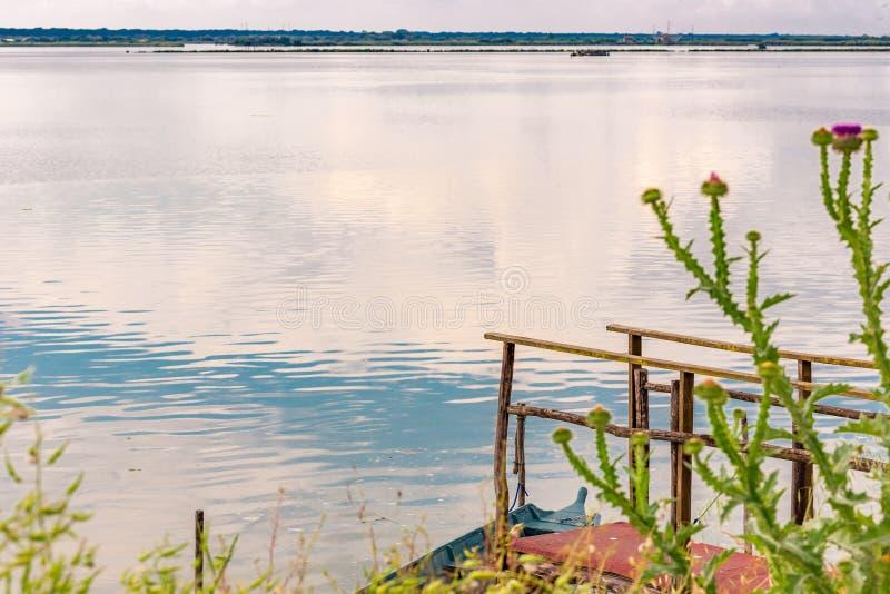 Пристань и причаленная шлюпка на brackish лагуне стоковое фото