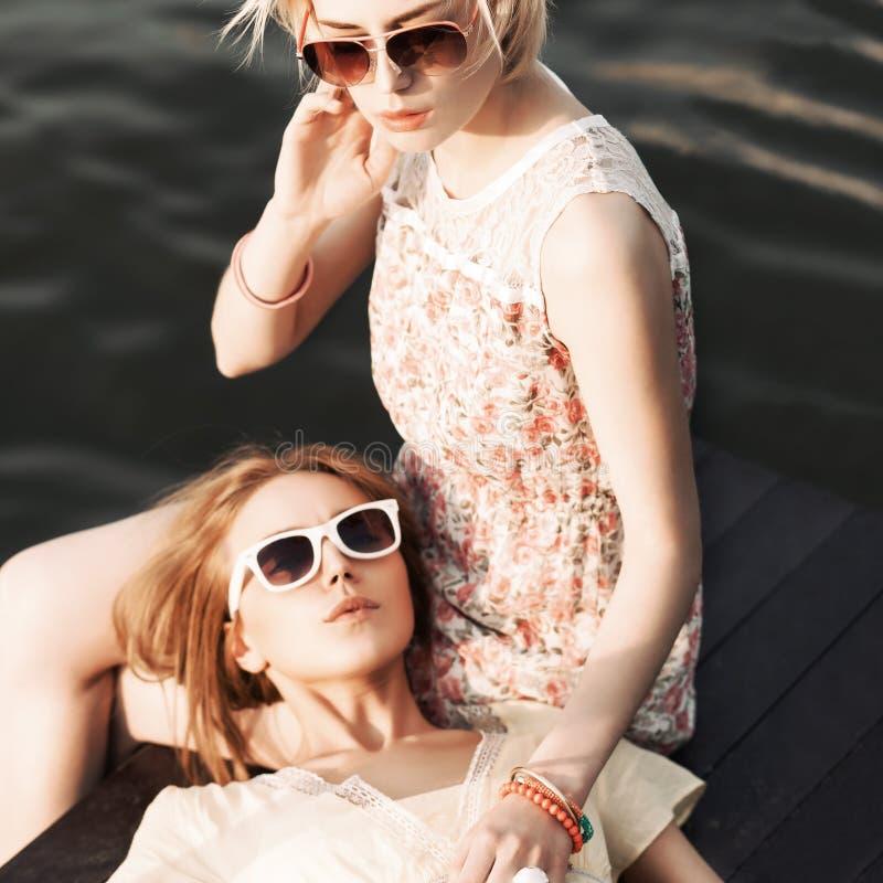 Пристань 2 красивая девушек на море стоковые фото