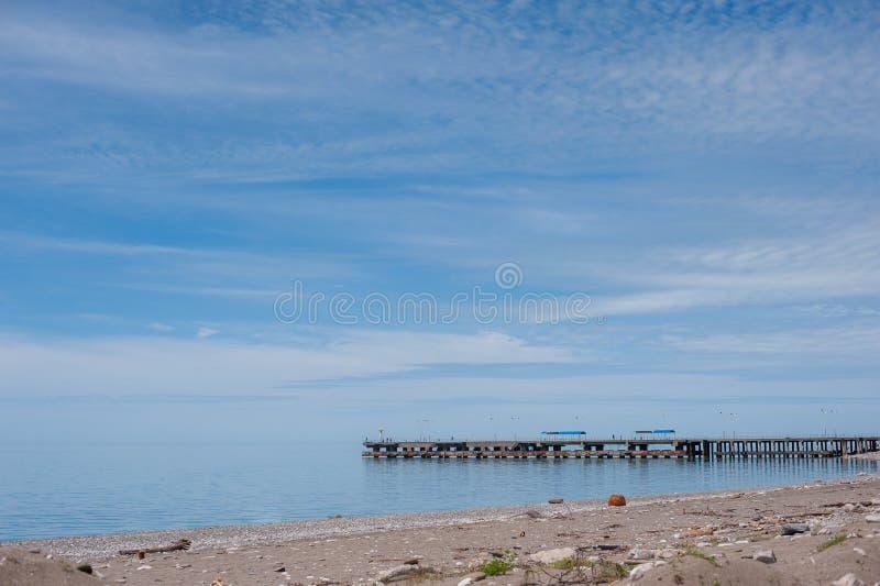 Пристань моря, голубое небо со светлыми облаками стоковые фотографии rf