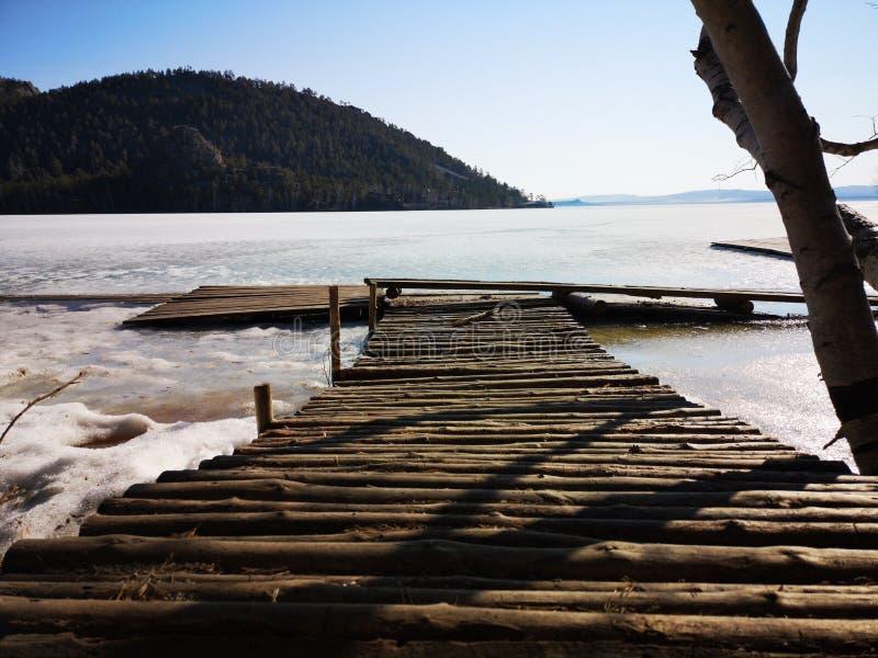 Пристань от входит в систему замороженное озеро в лесе горы стоковое фото