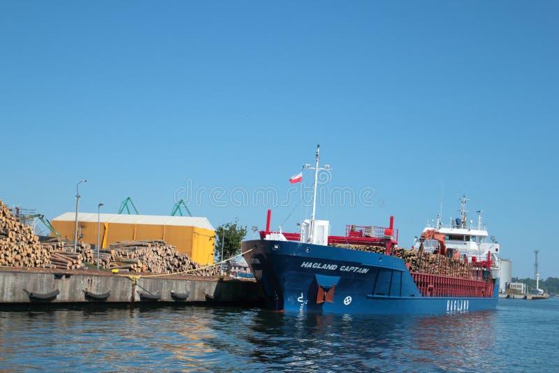 Пристань с загрузкой корабля с деревянными журналами стоковые фото