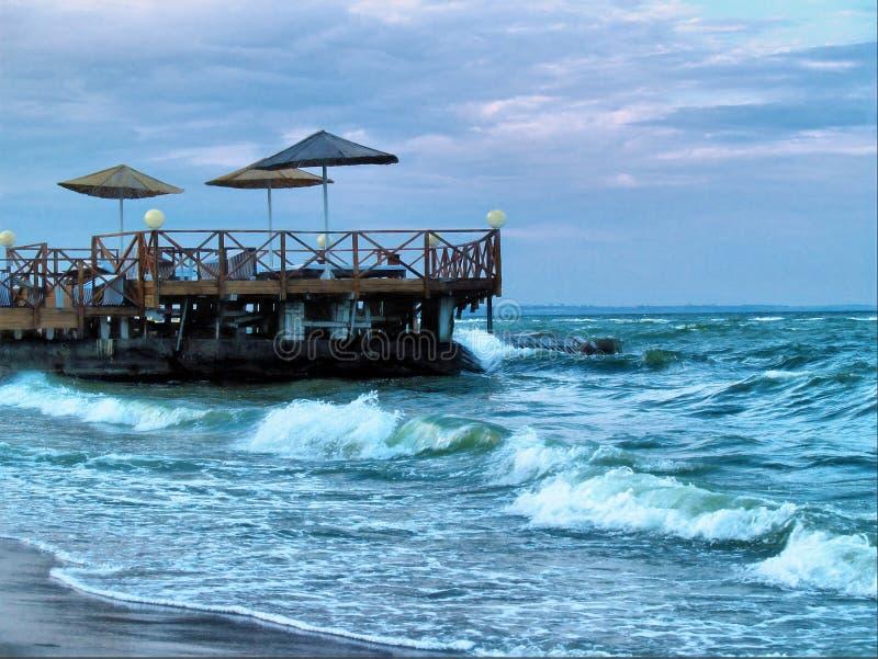 Пристань с зонтиками на заходе солнца и волнами шторма Чёрного моря Одессы, Украины - июля 2019 стоковое изображение rf