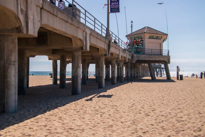 Пристань Huntington Beach как увидено на солнечный день от взгляда пляжа смотря вверх показывающ конкретные штендеры на нижней ст стоковые фото
