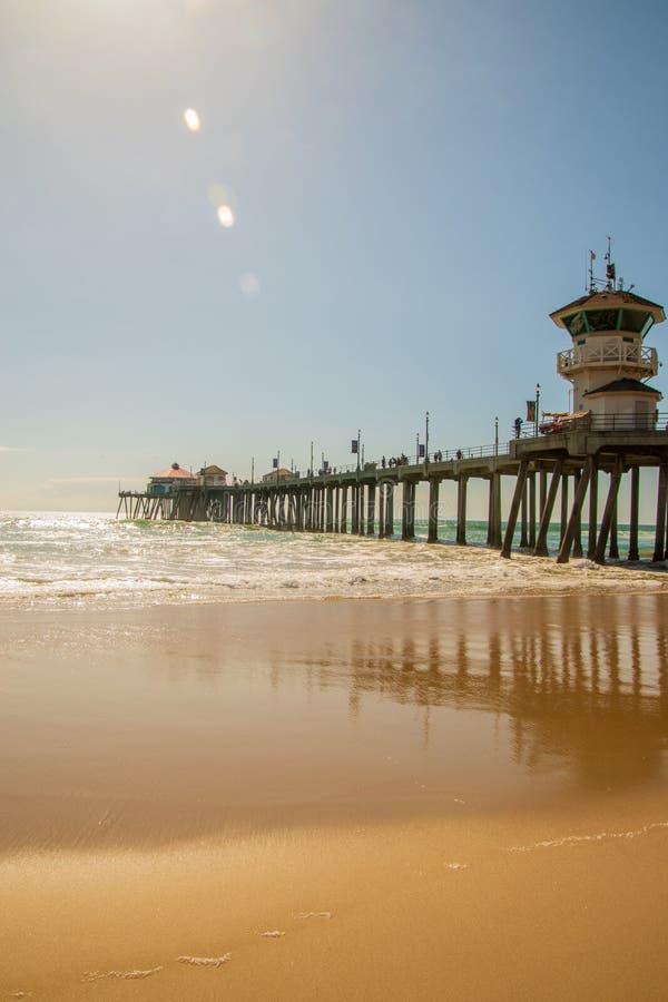 Пристань Huntington Beach как увидено на солнечный день от взгляда пляжа смотря вверх показывающ конкретные штендеры на нижней ст стоковые фотографии rf