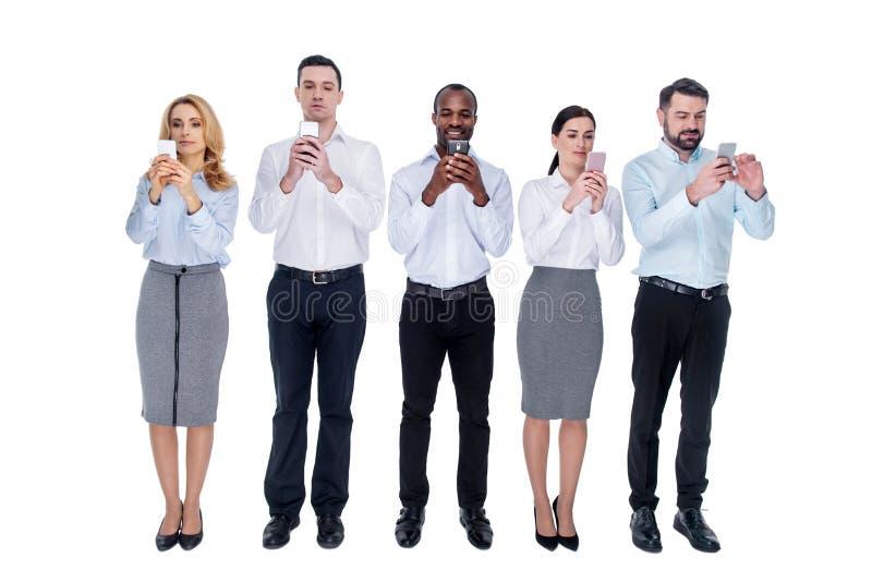 Пристрастившийся коллеги стоя в одной линии с их телефонами стоковая фотография